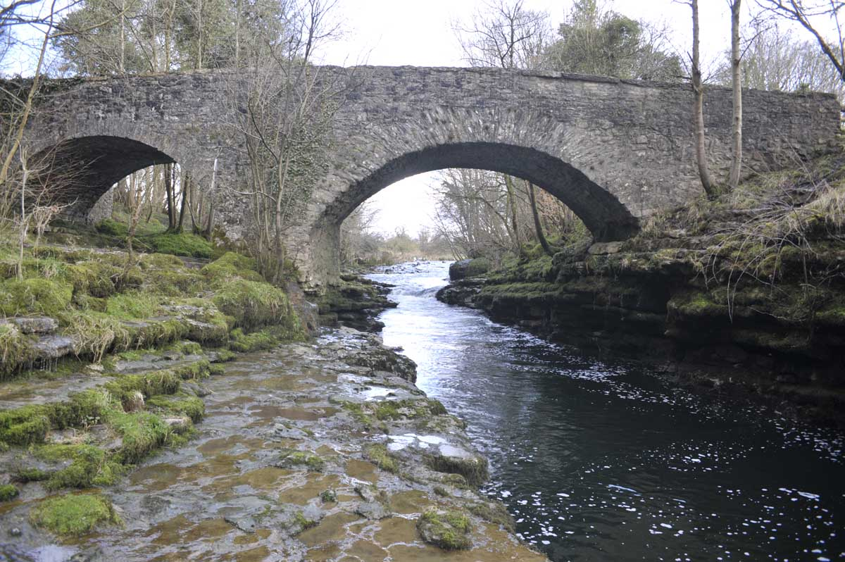 The River running under the two arches of Hawes Bridge.